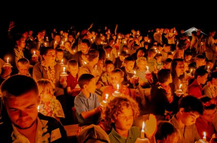 Kids holding candles together at night