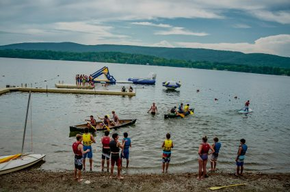 people racing in canoes and swimming